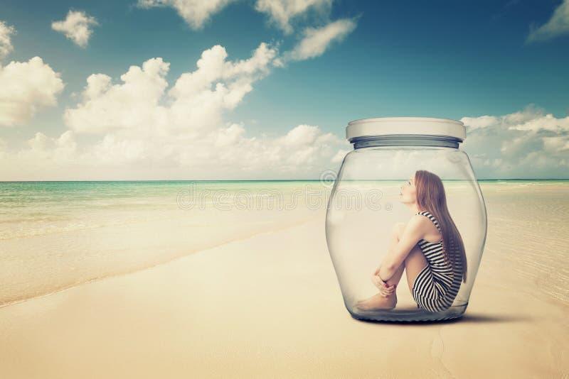 妇女在一个玻璃瓶子坐看海景的海滩 免版税库存图片