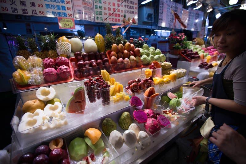 妇女在一地方夜市卖在她的摊位的新鲜水果 库存图片