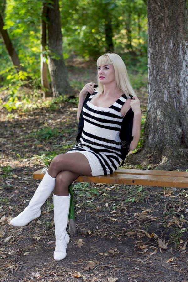 妇女在一条长凳的公园在秋天 库存图片