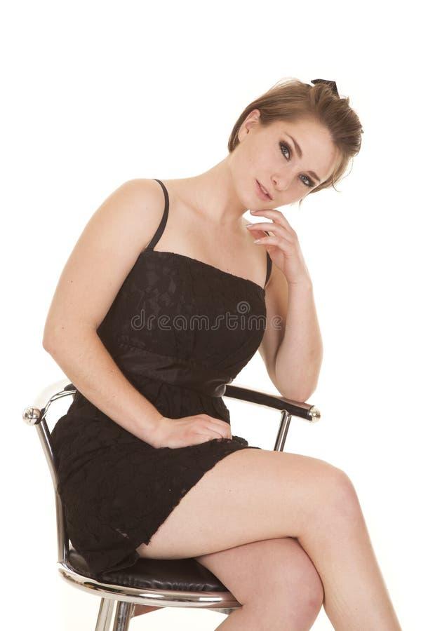 妇女在下巴的一只黑礼服坐的手上 免版税库存图片