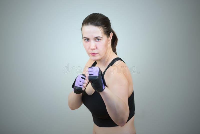 妇女在与在灰色演播室背景隔绝的一个紧握拳头的一个把装箱的姿势实践跆拳道并且站立 免版税库存图片