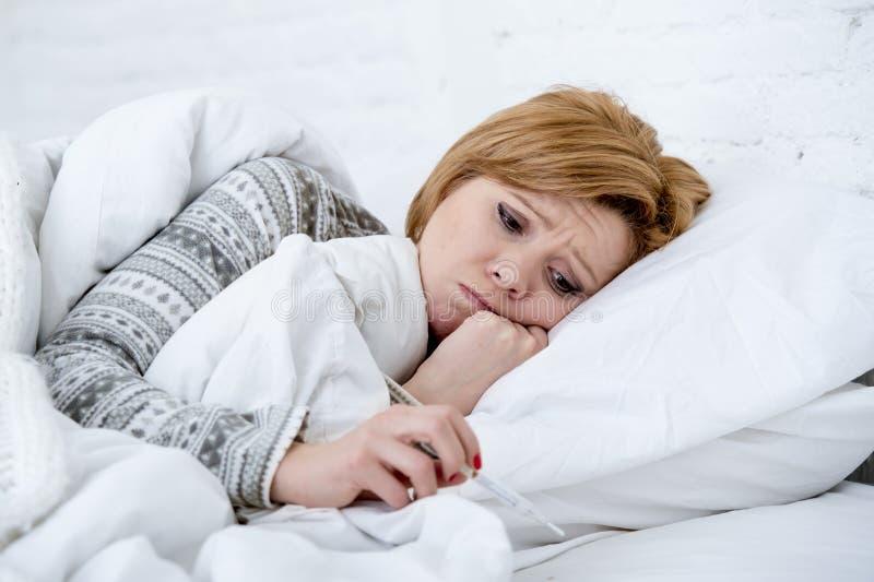 妇女在与温度计狂热微弱的遭受的冬天冷的流感病毒的床上 库存照片