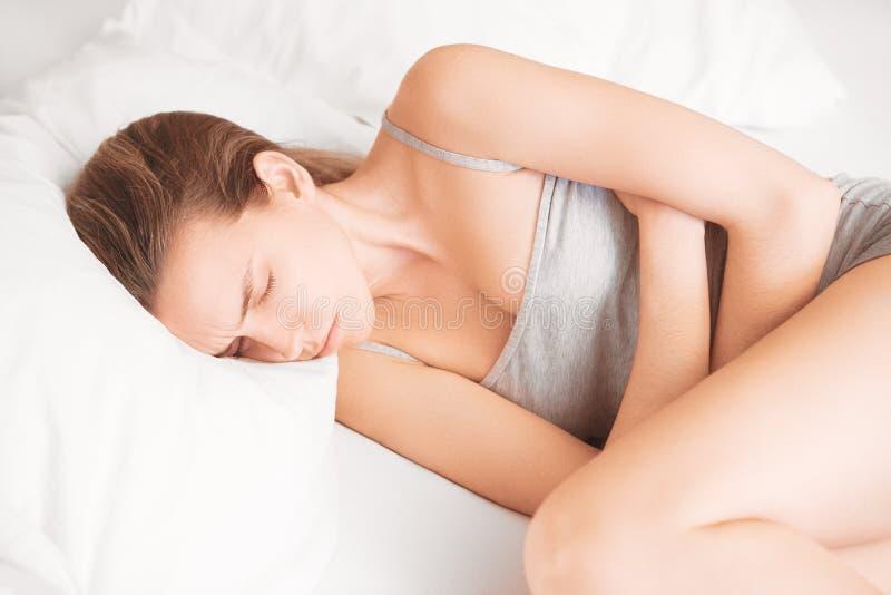 妇女在与stomachache,痛苦的床上 库存图片