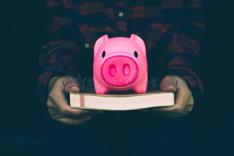 妇女在为教育目的、银行业务和保存的概念将使用的存钱罐保留金钱 库存照片