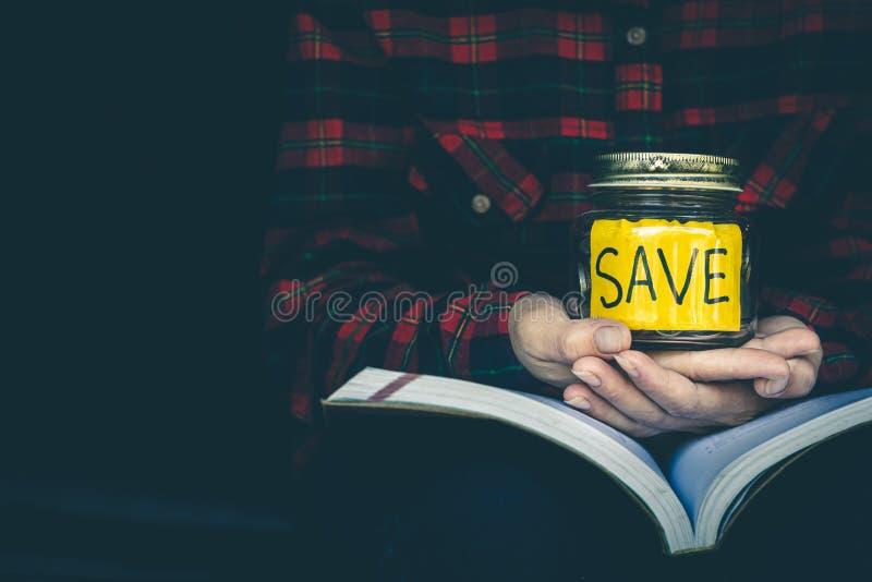 妇女在为教育目的、银行业务和保存的概念将使用的存钱罐保留金钱 图库摄影