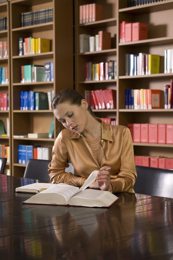 妇女在书桌的阅读书在图书馆里 免版税库存图片
