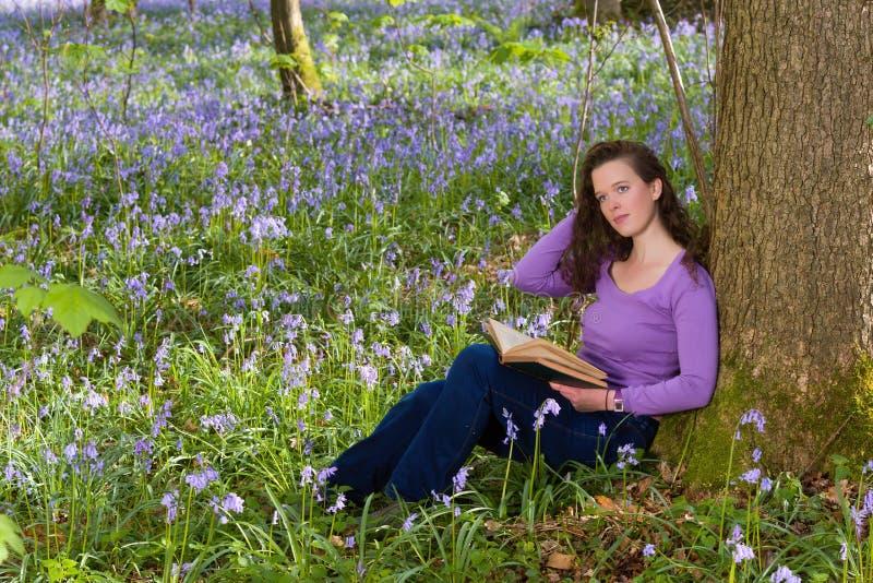 妇女在会开蓝色钟形花的草森林里 库存图片