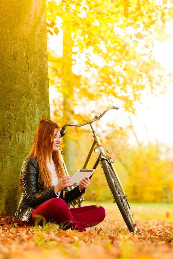 妇女在使用片剂计算机读书的秋天公园 图库摄影