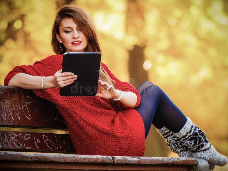 妇女在使用片剂计算机读书的秋天公园 库存照片