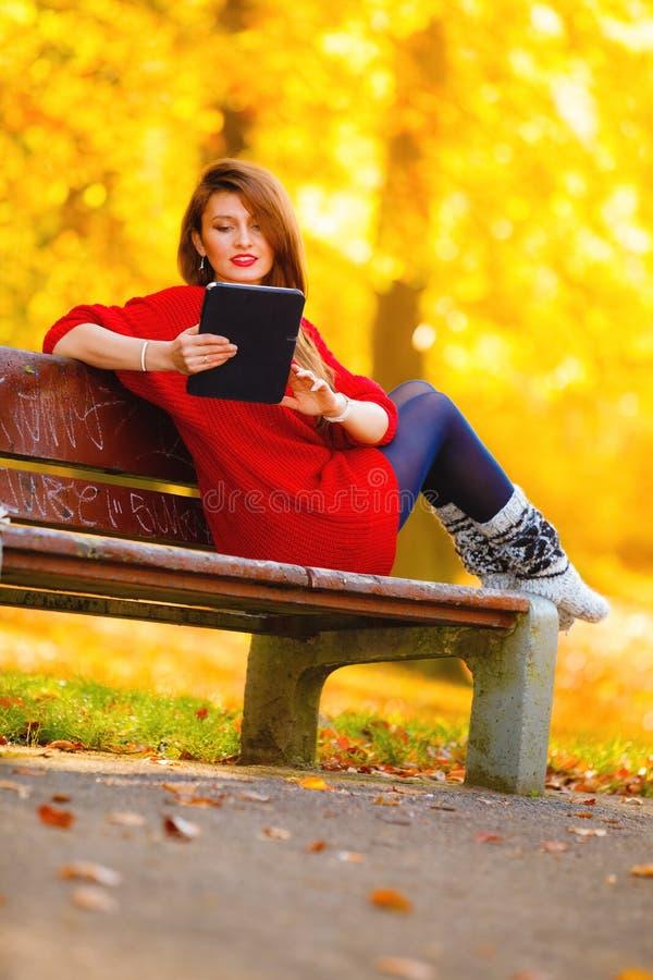 妇女在使用片剂计算机读书的秋天公园 免版税库存照片