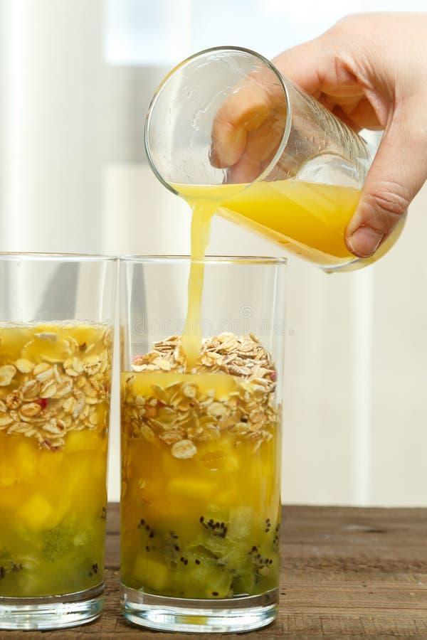妇女在倒果汁入与果子圆滑的人的玻璃的她的手上举行一stanacone 库存照片