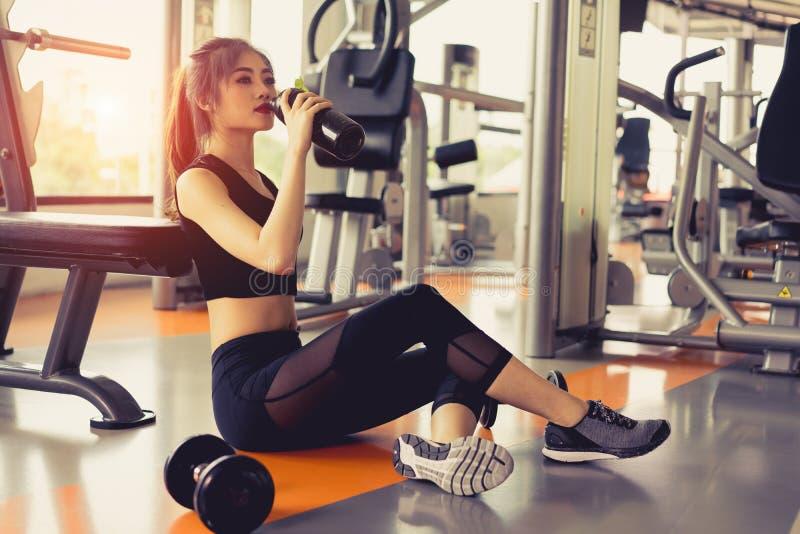 妇女在健身房健身打破的锻炼锻炼放松饮用的蛋白质震动 免版税库存图片