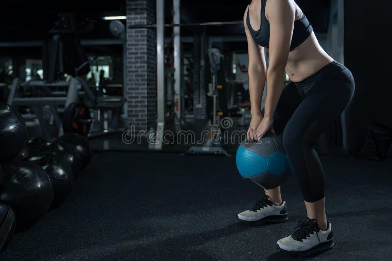 妇女在健身房健身训练体育的锻炼锻炼与kettlebells举重和腿蹲健康生活方式体型 库存照片