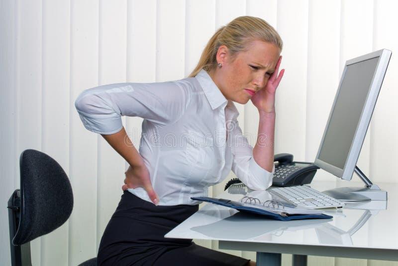 妇女在充满背部疼痛的办公室 免版税库存图片