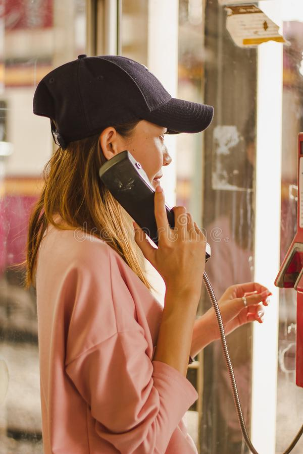 妇女在公用电话摊 免版税库存图片