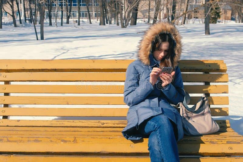 妇女在冬天城市公园浏览她的电话的互联网坐长凳在晴天 库存图片
