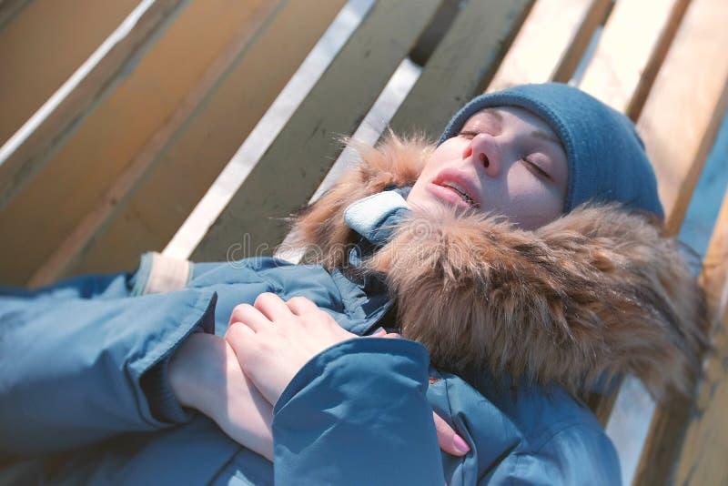 妇女在冬天成为了不适,说谎在一张公园长椅和沉重呼吸 库存照片