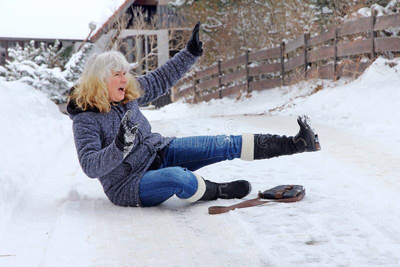 妇女在冬天路滑倒了并且跌倒了 库存图片