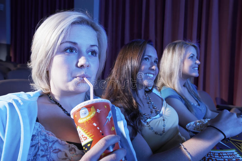 妇女在剧院喝与观看电影的朋友的软饮料 库存图片