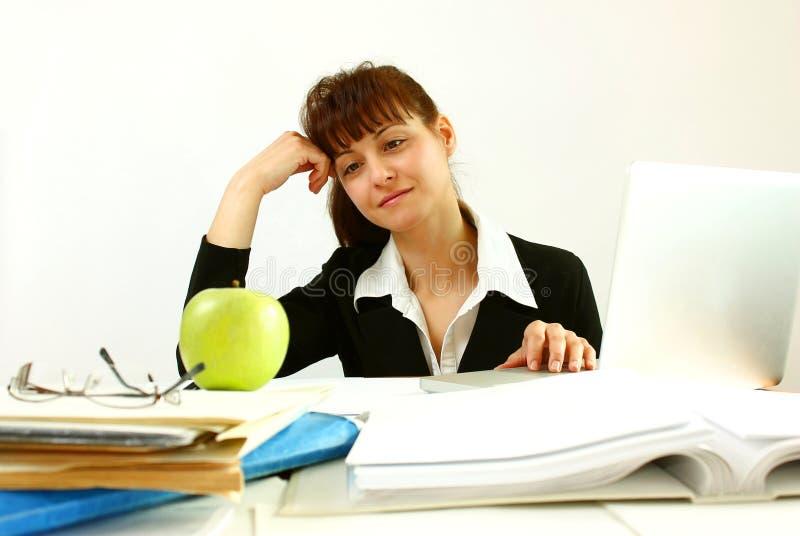 妇女在办公室用苹果 免版税库存图片