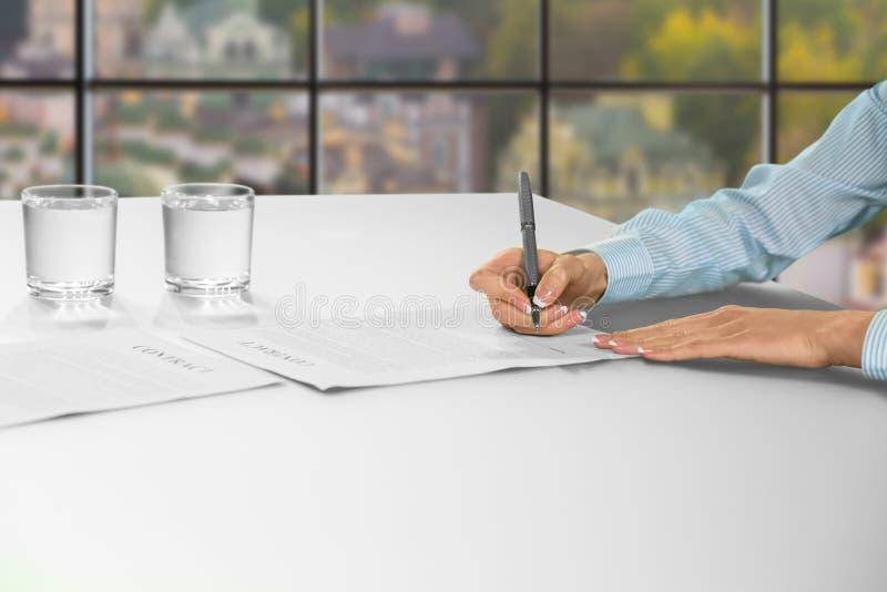 妇女在办公室签合同 免版税库存图片