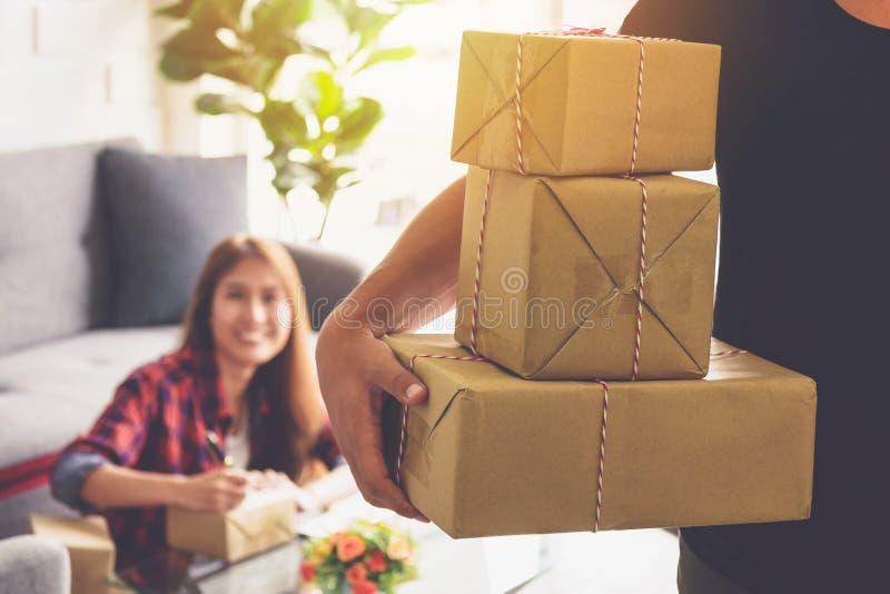 妇女在包含她的产品的箱子微笑面孔写着接收者的名字将被交付到在书桌上的顾客  库存图片