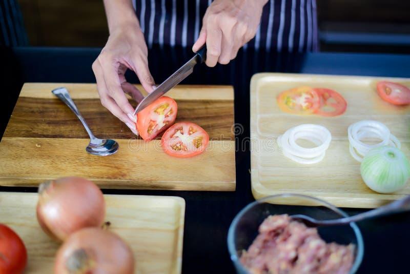 妇女在厨房里切与刀子的蕃茄在一个木切板 库存图片