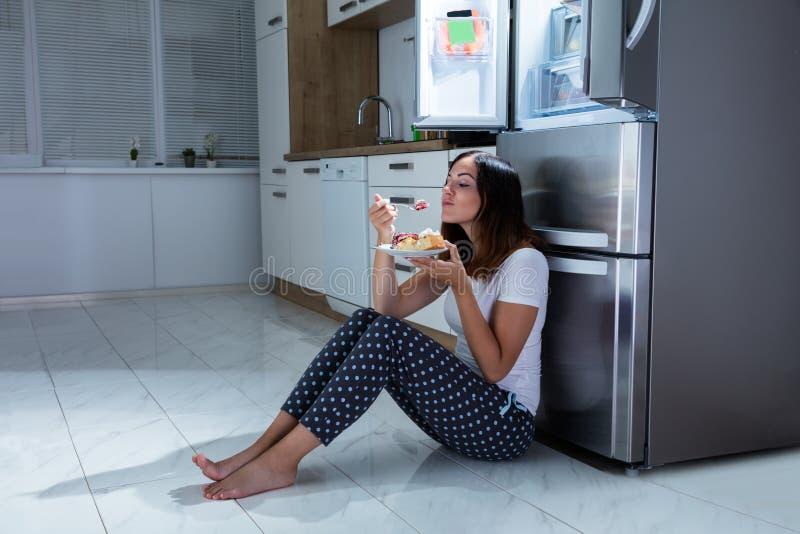 妇女在厨房里喜欢吃甜食物 免版税库存图片