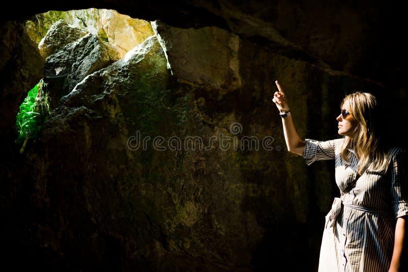 妇女在古老洞的指向和孔-阳光 库存图片
