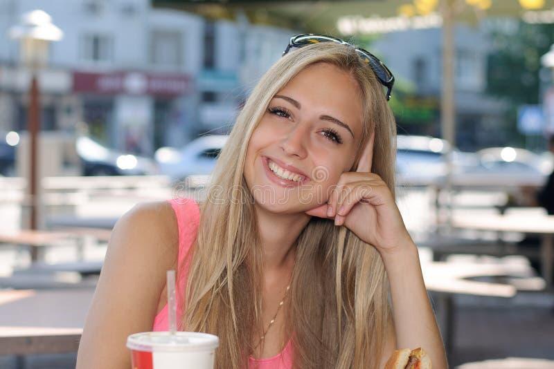 妇女在咖啡馆和微笑坐户外 免版税库存图片