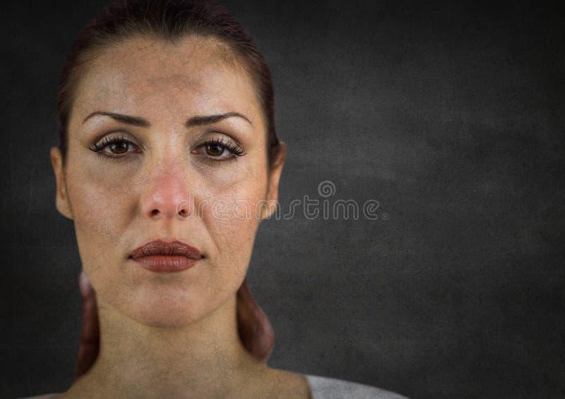 妇女在哭泣的` s面孔对有难看的东西覆盖物的灰色墙壁以后 库存照片
