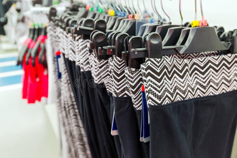 妇女在商店炫耀在挂衣架的裤子 库存图片