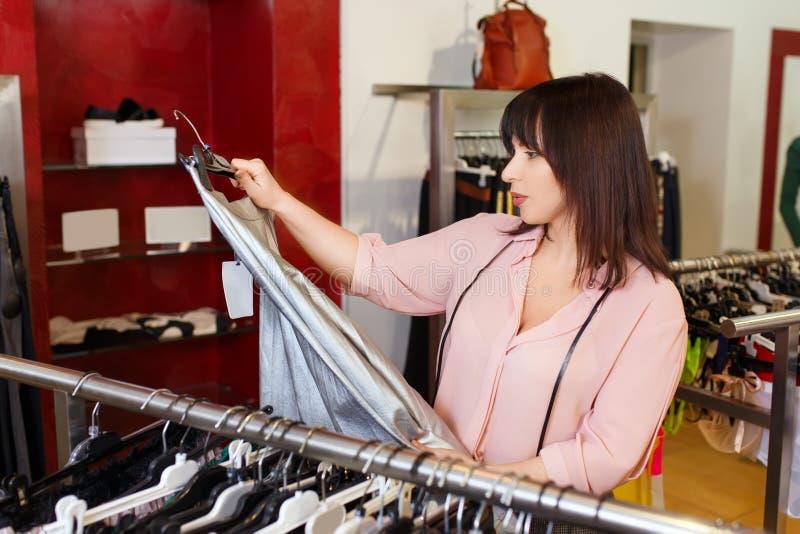 妇女在商店选择衣裳 免版税库存图片