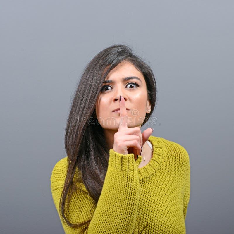 妇女在嘴唇的藏品手指画象作为反对灰色背景的沈默姿态 库存照片