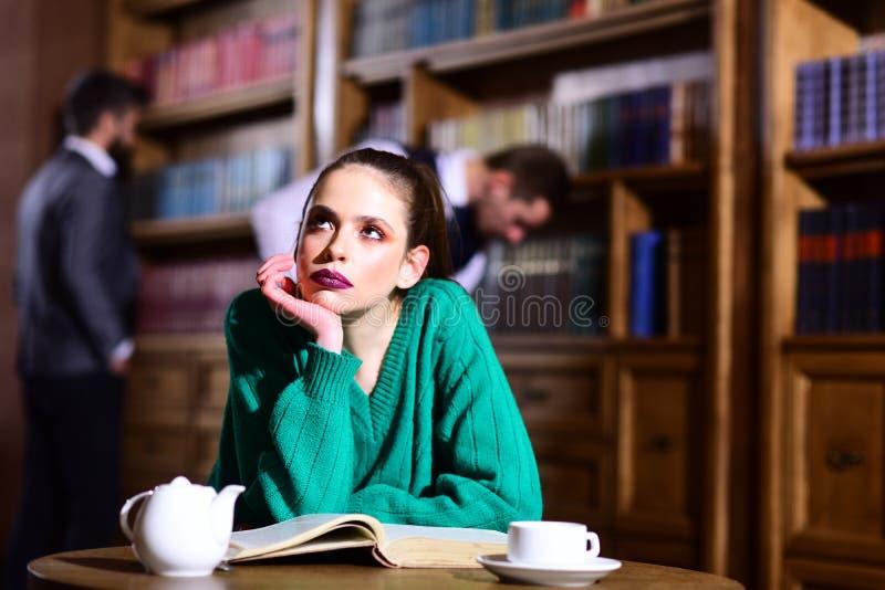 妇女在图书馆读了书在从杯子的茶壶饮用的咖啡 与逗人喜爱的女孩和人的文学咖啡馆 学生生活 免版税库存图片