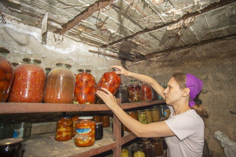 妇女在地下室长期投入有蔬菜和水果的瓶子用食物,存贮的 免版税库存图片