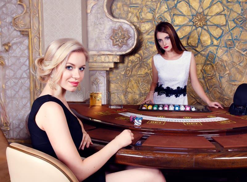 妇女在坐在啤牌桌上的赌博娱乐场 免版税库存照片