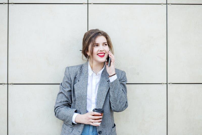 妇女在墙壁附近站立用咖啡 由电话沟通 r 生活方式的概念,都市,事务,研究 免版税库存图片