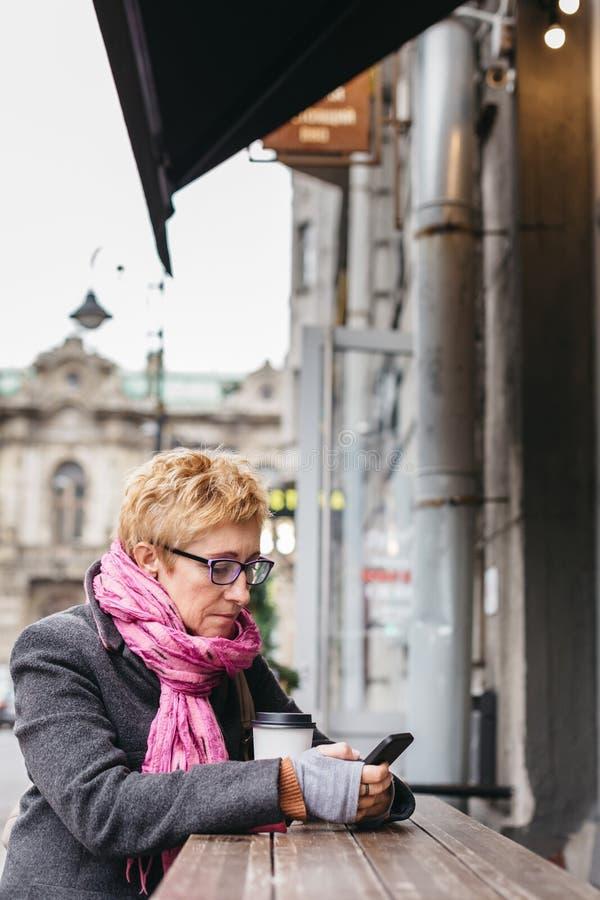 妇女在外部咖啡馆的浏览智能手机 免版税库存照片