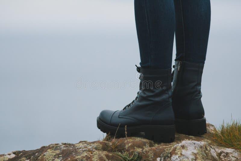 妇女在大起动的远足者腿在山峰峭壁 免版税库存照片