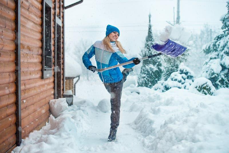 妇女在她的围场清洗雪在乡间别墅里 免版税库存照片