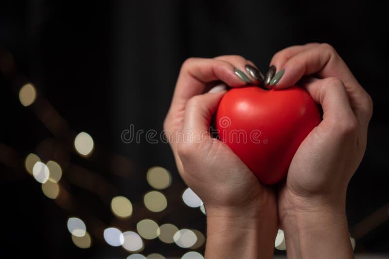 妇女在她的手上拿着大红心 库存图片