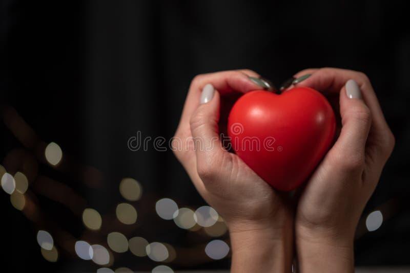 妇女在她的手上拿着大红心 库存照片