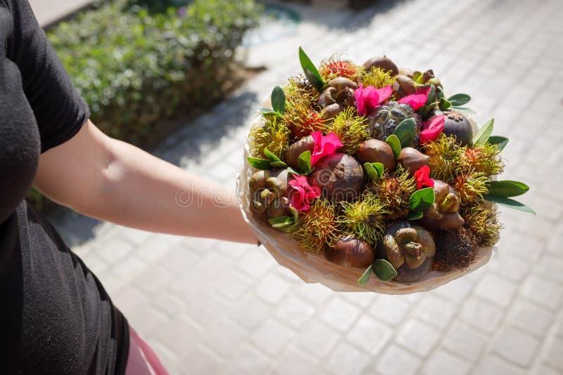 妇女在她的手上拿着异乎寻常的果子独特的鲜美花束  库存图片
