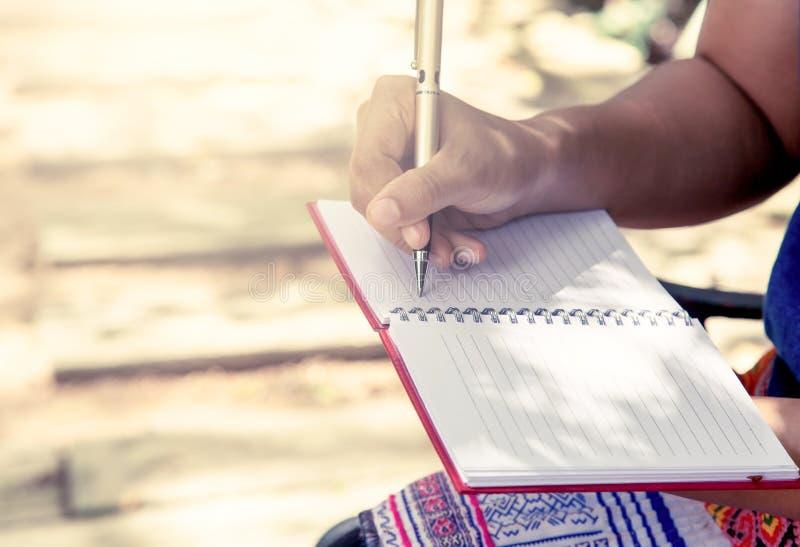 妇女在她的笔记本的手文字在公园 图库摄影