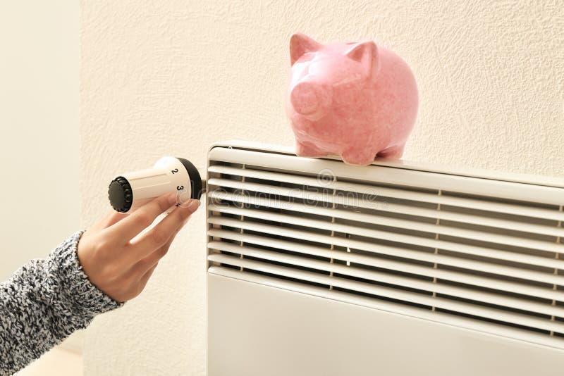 妇女在存钱罐附近的藏品温箱calorifer的 加热的保存的概念 免版税图库摄影