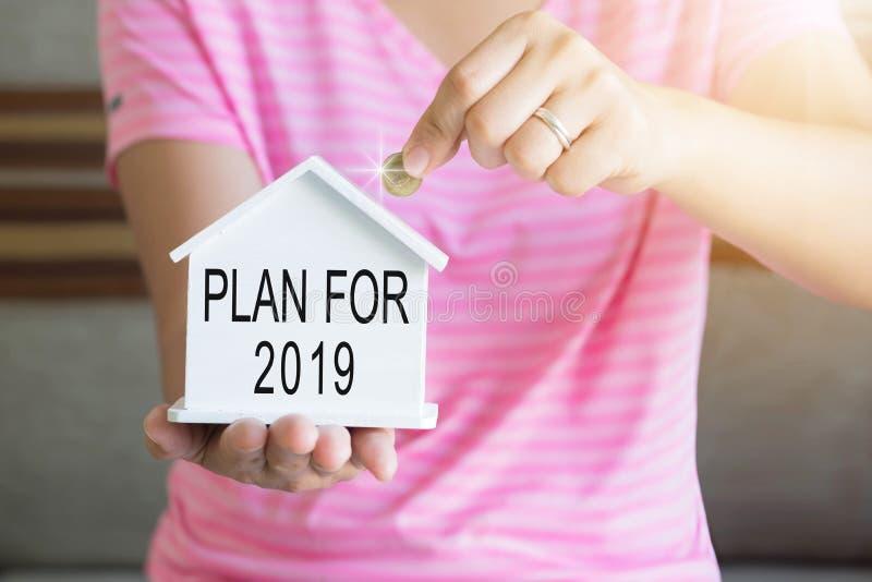 妇女在存钱罐,攒钱概念,财政储款的概念中递投入金钱硬币买房子,计划在2019年 库存图片
