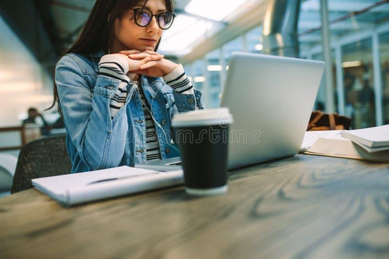 妇女在学院自助食堂读书信息坐膝上型计算机 看手提电脑的女生,当坐在时 免版税库存图片