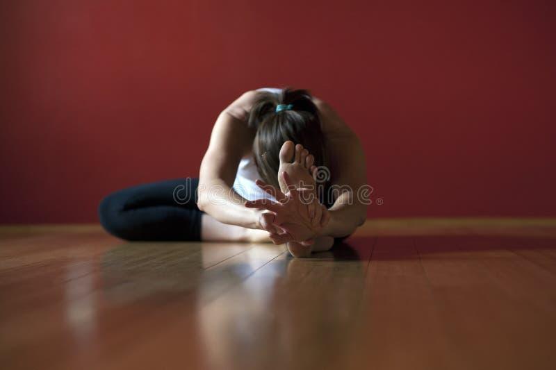 妇女在实践Janu Sirsasana的瑜伽演播室 图库摄影