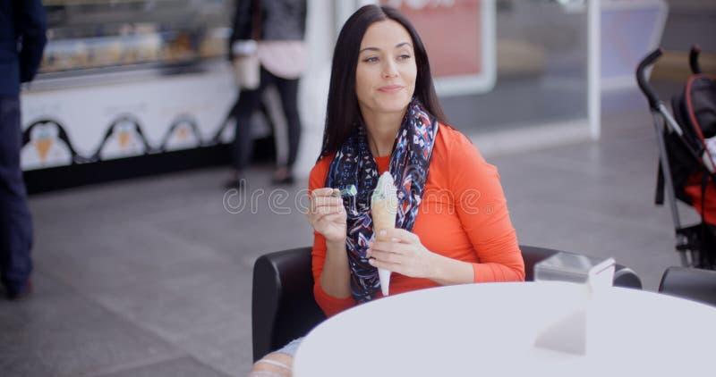 妇女在客厅或咖啡馆里的吃冰淇凌 库存图片